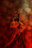 Goddess of Compassion Bronze Statue Red Grunge. Kuan Yin Goddess of Compassion Bronze Statue Standing on red grunge texture blurred defocused bokeh background royalty free stock photo