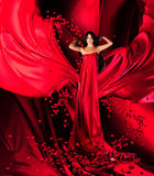 Goddess of love in red dress and hearts. Goddess of love in long red dress with magnificent long hair makes a magic ritual of connecting hearts of people on red Royalty Free Stock Images