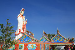 Goddess of Mercy statue behind Chinese temple. Roof against blue sky at wat Saman Rattanaram in Chachoengsao, Thailand Stock Images