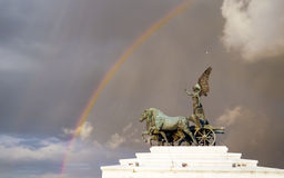 Goddess Victoria riding on quadriga (Altar of the Fatherland) against the background of stormy sky and rainbow. Royalty Free Stock Photo