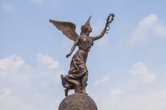 Goddess of victory Nike against the clouds and sky. Royalty Free Stock Photography