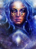 Goddess Woman with tattoo on face in space with light stars. Stock Photos