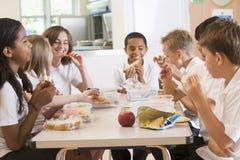 godendo degli scolari del banco del pranzo loro Fotografie Stock Libere da Diritti