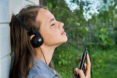 Godendo della musica all'aperto con le cuffie e uno smartphone immagini stock libere da diritti