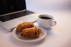 Godendo dello spirito di lavoro un caffè e spuntini della tazza Fotografie Stock