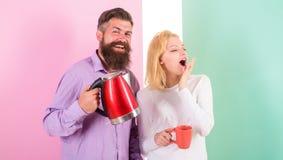 Godere del caffè di mattina Uomo con la teiera e la donna elettriche con la tazza pronta a bere il caffè di mattina Ottenga il co Fotografia Stock