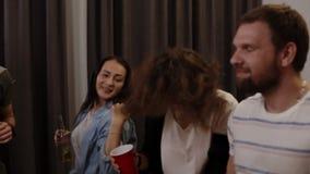 Godere del partito con gli amici Metraggio dei giovani allegri che ballano e che bevono mentre godendo a casa del partito in archivi video