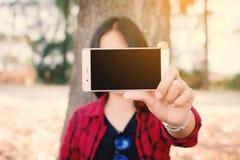 Godere della donna di momento che per mezzo dello smartphone che si siede sotto il grande albero sul parco fotografia stock