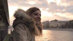 Godere della donna galleggia sulla barca di giro sul fiume in città nella caduta o sulla primavera al tramonto immagini stock libere da diritti