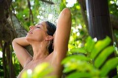 Godere della donna si rilassa nella doccia all'aperto della stazione termale Immagine Stock