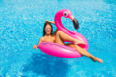 Godere della ragazza di vacanza con gli occhiali da sole nella piscina immagini stock