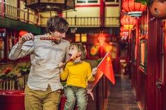 Godere della vacanza in Cina Turisti felici papà e figlio con una bandiera cinese e con i frutti canditi del cinese tradizionale immagini stock