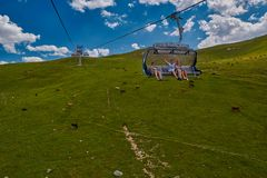 GODERZI SKI RESORT, GEORGIA - 08 AUGUST 2017: happy tourists wav. Ing hands in cableway carriage over mountain landscape of Adjara region Royalty Free Stock Photo