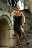 Godess. Girl posing in old ruins in a black dress Royalty Free Stock Photography