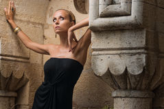 Godess. Girl posing in old ruins in a black dress Stock Image