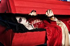 Godforsaken. Bloodthirsty female vampire rises from the coffin on the night cemetery Royalty Free Stock Images