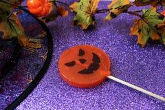 Godis i form av en pumpa för allhelgonaafton på den briljanta bakgrunden med garneringar för allhelgonaafton halloween Arkivfoto