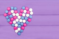 Godisar av olika färger som bildar en hjärta på en purpurfärgad bakgrund royaltyfria bilder