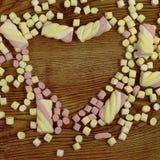 Godisar som förläggas i hjärtaform Dag för valentin` s och förälskelsebegrepp på träbakgrund Fotografering för Bildbyråer