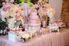 Godisstång och bröllopstårta Tabell med sötsaker, buffé med muffin, godisar, efterrätt Royaltyfri Foto
