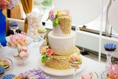 Godisstång på guldbrölloppartiet med mycket olika godisar, muffin, souffle och kakor Dekorerat i brun och purpurfärgad colo arkivfoto