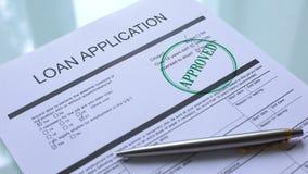 Godkänd lånansökningshandling, hand som stämplar skyddsremsan på den officiella pappers- closeupen arkivfilmer