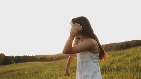 Godlynt le för lycklig kvinna, skratta och dansa i fältet i solljuset på solnedgången arkivfilmer