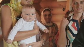 Godmother holds a godson in arms during the baptism ritual in church stock video