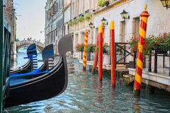 Godolas in  Venice, Italy. The waterways in Venice Italy have many gondolas.  The stripes on the mooring poles in Venice remind us of barber poles Royalty Free Stock Photography