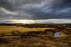Godrays往山的日落视图冰岛用草水a 免版税库存照片