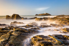 Godrevy Lighthouse, Cornwall. United Kingdom. Green sea with blue sky, misty water and long exposure, rocks, island Royalty Free Stock Images