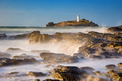 Godrevy Lighthouse, Cornwall. United Kingdom. Green sea with blue sky, misty water and long exposure, rocks, island Royalty Free Stock Photos