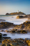 Godrevy Lighthouse, Cornwall. United Kingdom. Green sea with blue sky, misty water and long exposure, rocks, island Stock Image