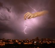 Gods exasperation. Hand holding - sending flash on the town under the dark cloudy sky Royalty Free Stock Photo