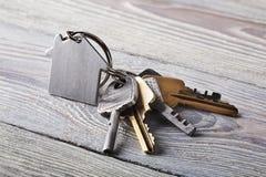 Godsbegrepp, keychain med hussymbolet, tangent på träbakgrund Arkivbilder