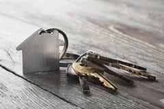 Godsbegrepp, keychain med hussymbolet, tangent på träbakgrund Royaltyfria Bilder