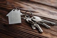 Godsbegrepp, keychain med hussymbolet, tangent på träbakgrund Royaltyfri Foto
