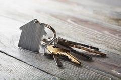 Godsbegrepp, keychain med hussymbolet, tangent på träbakgrund Fotografering för Bildbyråer