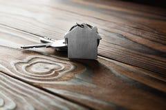 Godsbegrepp med symbolet av huset, tangent på träbakgrund Arkivfoton