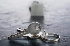 Godsbegrepp med tangenten, keychain med hussymbolet, stenbakgrund Arkivfoton