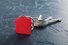 Godsbegrepp med tangenten, röd keychain med hussymbol, betong Royaltyfria Foton