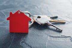 Godsbegrepp med tangenten, röd keychain med hussymbol, betong Royaltyfri Bild
