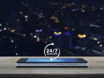 24 godziny usługują ikonę na nowożytnym mądrze telefonu ekranie na drewnianej zakładce Obrazy Royalty Free