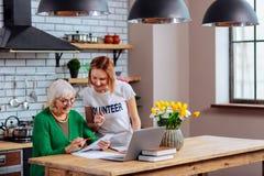 Goed-een beroep doet medewerker die verouderde oma helpen om documenten te ondertekenen stock afbeelding