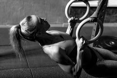 Goed gebouwde aantrekkelijke vrouw die haar spieren opbouwen Stock Foto's