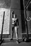 Goed gebouwde harde werkende vrouw die haar hand omhoog houden Royalty-vrije Stock Foto's