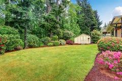 Goed gehouden tuin bij binnenplaats met bomen, struiken en bloemen royalty-vrije stock afbeelding