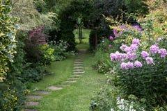 Goed gehouden tuin met gazon, springplanken en goed opgeslagen bloembedden Oxford, het UK stock afbeelding