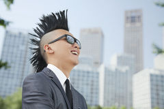 Goed-geklede jonge mens met Mohawk en zonnebril die, wolkenkrabbers op achtergrond glimlachen Royalty-vrije Stock Afbeeldingen