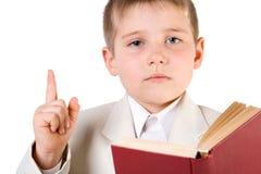 Goed-geklede jongen gelezen boek en liftvinger omhoog Stock Foto's